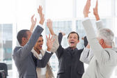Group of smiling business raising their hands — Stock Photo