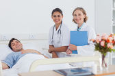 Patient and doctors looking at the camera — Stock Photo