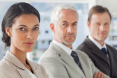 Serious businesswoman smiling with colleagues behind — Stock Photo