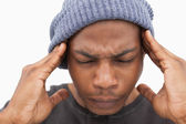 Man in beanie hat grimacing with pain of headache — Stok fotoğraf
