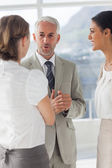 Mature businessman discussing with female colleagues — Stock Photo