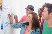 Creative team watching colleague add to flowchart — Stock Photo