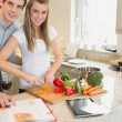 Woman cutting vegetables with man reading the cookery book — Stock Photo