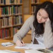 Bored student in a library learning — Stock Photo #25730613