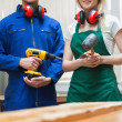 Stock Photo: Two woodworking students standing before a workbench