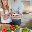 Happy couple with cookery book — Stock Photo #25730723