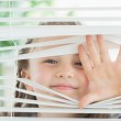 Happy child peeking through blinds — Stock Photo