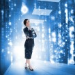 Businesswoman standing and looking thoughtful in data center — Stock Photo #25730897