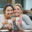 Two smiling students in college coffee shop — Stock Photo