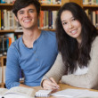 Two happy students in a library — Stock Photo #25731225