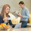 Woman with beverage and tablet computer and man with newspaper — Stock Photo