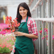 Garden center employee standing and holding flower pot — Stock Photo