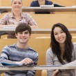 Happy students sitting in a lecture hall - Stock Photo