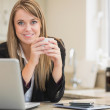 Happy woman holding hot beverage with laptop — Stock Photo