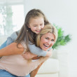Mother giving daughter a piggy back — Stock Photo