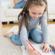 Little girl drawing sitting on floor with mother reading newspaper — 图库照片