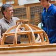 Teacher and student talking about a wooden frame - Stock Photo