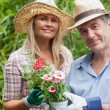 Blonde woman and man holding potted plant — Stock Photo #25732559