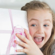 Surprised girl shaking a present — Stock Photo #25732937