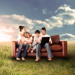 Happy family using the laptop in a field — Stock Photo #25733273
