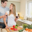 Couple enjoying drinking wine and cooking — Stock Photo