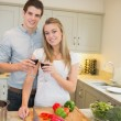 Man and woman cooking and clinking wine glasses — Stock Photo