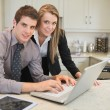 Foto Stock: Smiling couple using laptop
