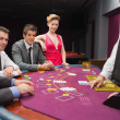 Sitting at blackjack table and smiling — Stockfoto