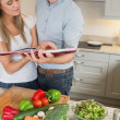 Couple reading cookery book — Stock Photo