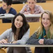 Girls smiling in lecture hall with tablet pc — Stock Photo