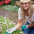 Woman gardening and touching flower — Stock Photo
