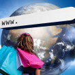 Girl with shopping bags looking at address bar with large earth — Stockfoto