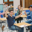 Stock Photo: Students in classroom giving thumbs up
