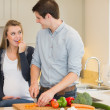 Man cutting vegetables for his pregnant wife — Stock Photo