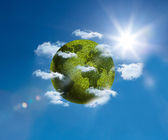 Green planet floating bright blue sky — Stock Photo