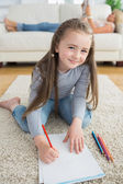 Happy girl drawing with her mother reading newspaper — Stock Photo