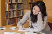 Bored student in a library learning — Stock Photo