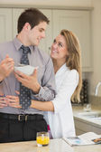 Man eats cereal while partner is embracing him — Stock Photo