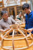 Teacher and a student in a woodworking class working on a frame — Stock Photo