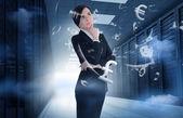 Empresária em pé no centro de dados com gráficos de moeda — Fotografia Stock