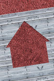 Cut wooden boards forming house with red texture — Stock Photo