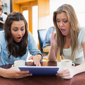 Women looking shocked at tablet pc in canteen — Stock Photo