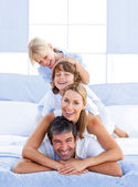 Family piled on top of dad — Stock Photo