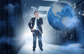 Businessman standing in data center with currency graphics and earth — Stock Photo