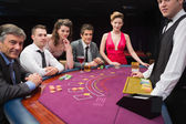 Sitting at the blackjack table smiling at the casino — Stock Photo