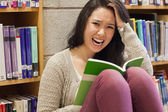 Stressed student reading in a library — Stock Photo