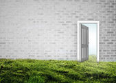 Doorway opening to blue sky in grey brick room — Stock Photo
