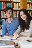 Two happy students in a library — Stock Photo