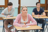 Three students in a classroom about to take notes — Stock Photo