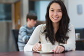 Happy student sitting in a coffee shop — Stock Photo